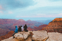people sitting on the edge of a cliff looking out over a canyon