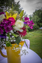 flower arrangement in a yellow pitcher on a table