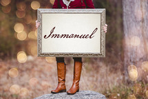 a woman holding a sign the reads Immanuel