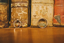 wedding band and engagement ring in front of old books