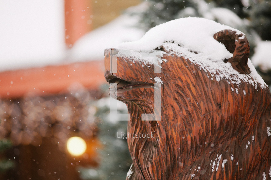 Wood carving of bear head in snow with lighted lodge in the background.