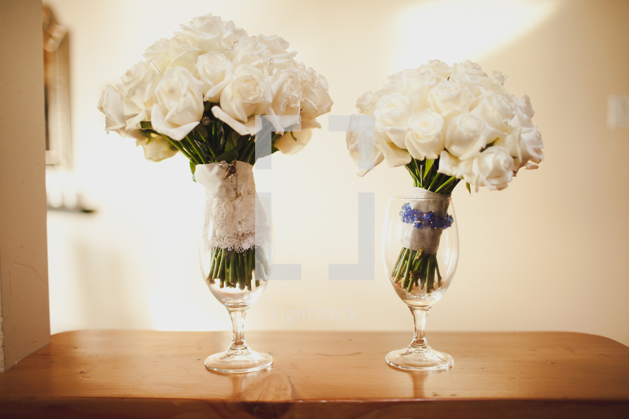 bridal bouquets in wine glasses