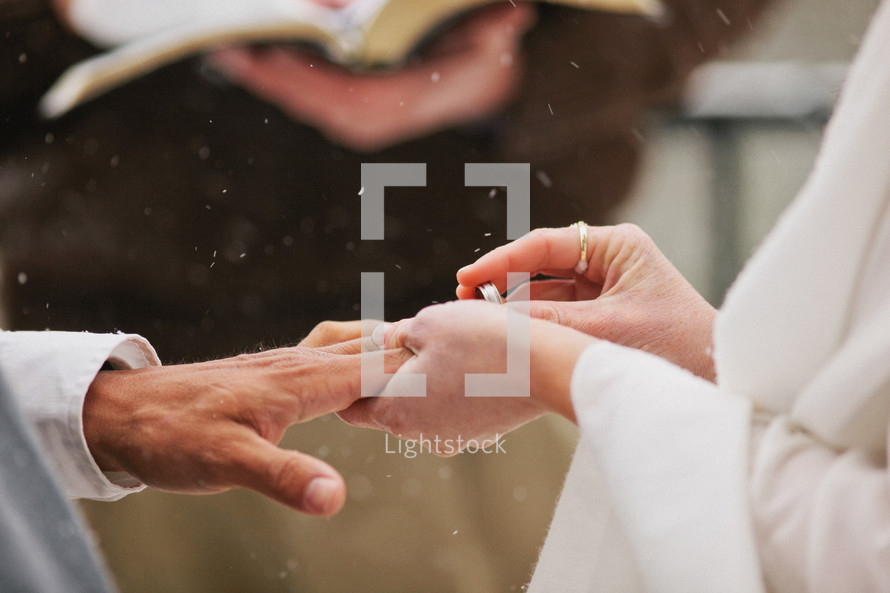 bride putting a ring on her grooms finger in the snow