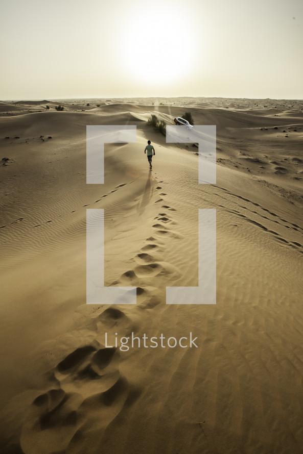 man running on sand dunes in a desert in Dubai