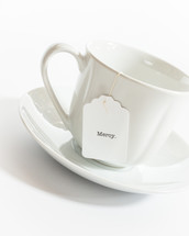 tea cup with the word mercy on the tea bag