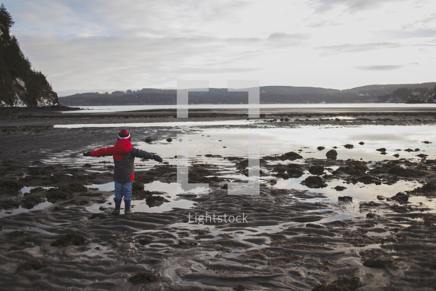 boy child standing in a tide pool