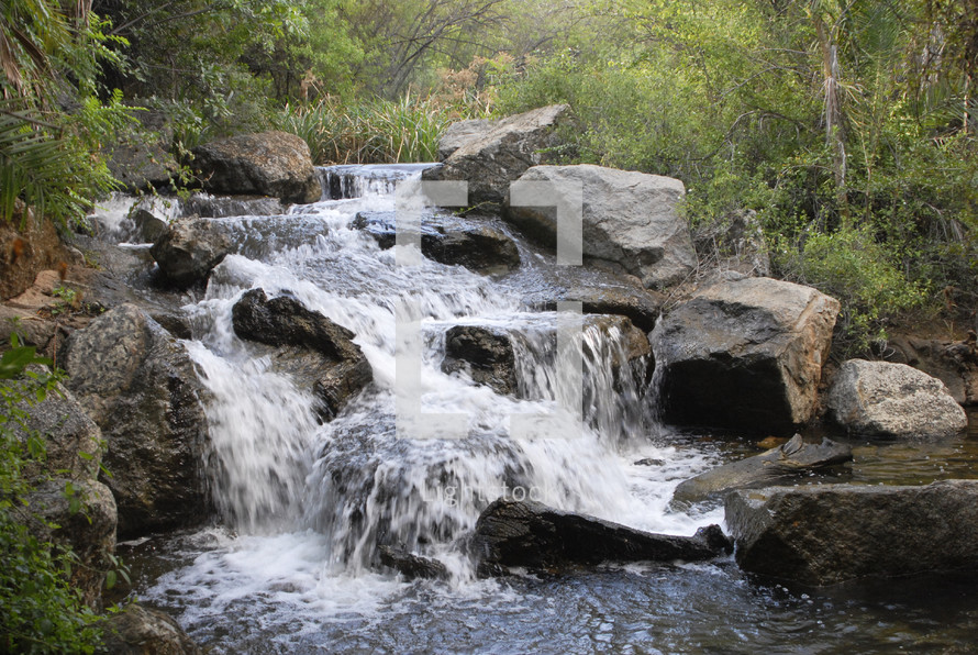 water rushing over a small waterfall