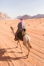 riding a camel through a desert