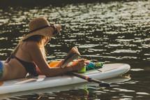 woman reading lying on a paddle board