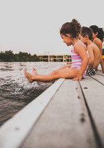 children sitting on a dock with their feet in the water