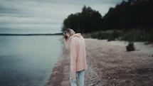 a woman walking along a shore