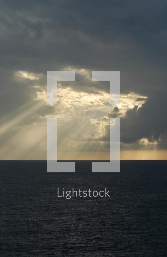 Sun beaming through clouds onto ocean