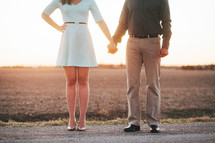 a couple holding hands outdoors at sunset