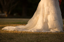 Train of a wedding gown on the grass in the daytime.