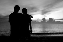 silhouettes of brothers on a beach
