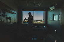 Silhouette of doctor talking to patient lying in hospital bed.