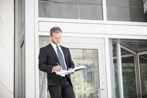 businessman writing in a notebook outdoors