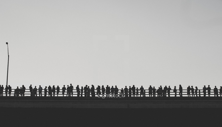 people looking off the side of a bridge