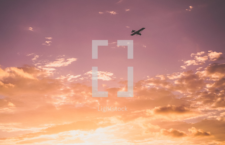 small plane in the sky at sunset