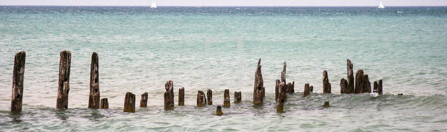 A row wood post on an ocean shore