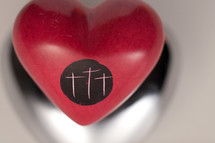 Three crosses engraved into a red ceramic heart.