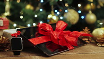Tablet pc, smartphone and smartwatch with gifts and decorations in front of Christmas tree.