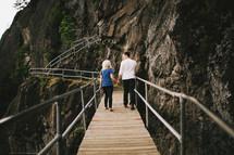 couple walking holding hands on mountain walking bridge