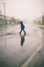 Child n a raincoat crossing the wet street.