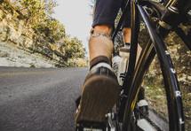 Feet and legs of biker biking uphill.