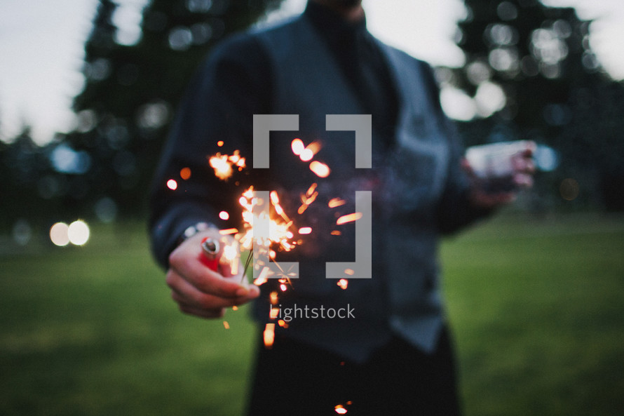 man holding a sparkler and a lighter