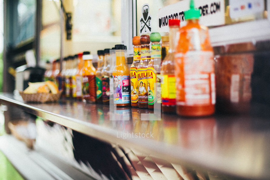 hot sauces on a restaurant's counter