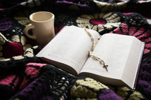 An open Bible and coffee cup on a colorful blanket.