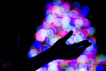 silhouette of a hand against bokeh lights