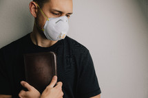 man in a N95 mask  holding a Bible