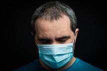 man in a face mask praying