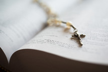 A cross necklace on an open Bible.