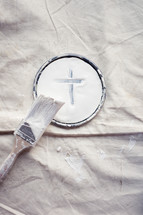 paint brush and cross on a paint can lid