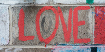 "Graffiti spray painted on a brick wall reading, ""love."""