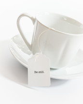 tea cup with the words be still on the tea bag
