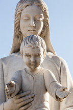 Statue of holy Virgin Mary mother of the child Jesus on blue sky