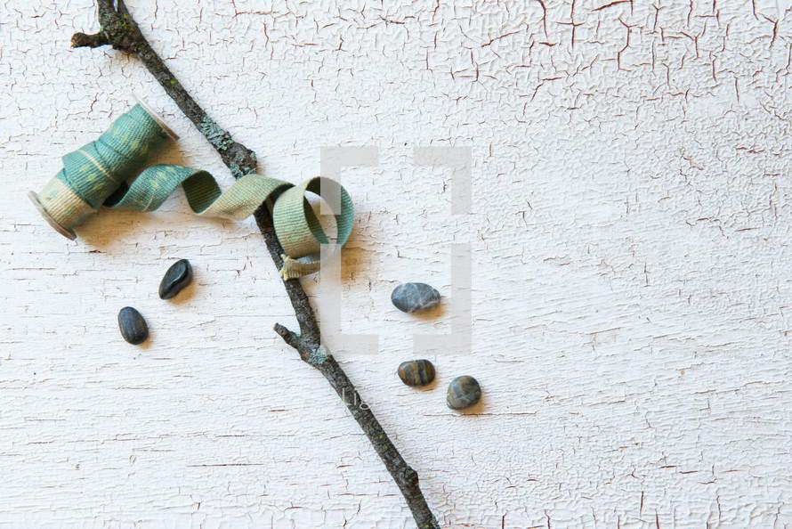stick, ribbon, and stones