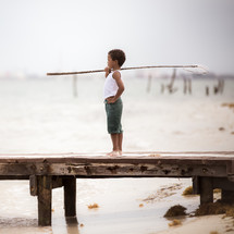 a boy holding a fishing net standing on a dock