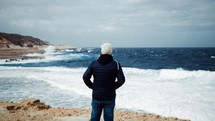 standing on a rugged shore