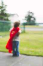 blurry image of a boy child in a cape