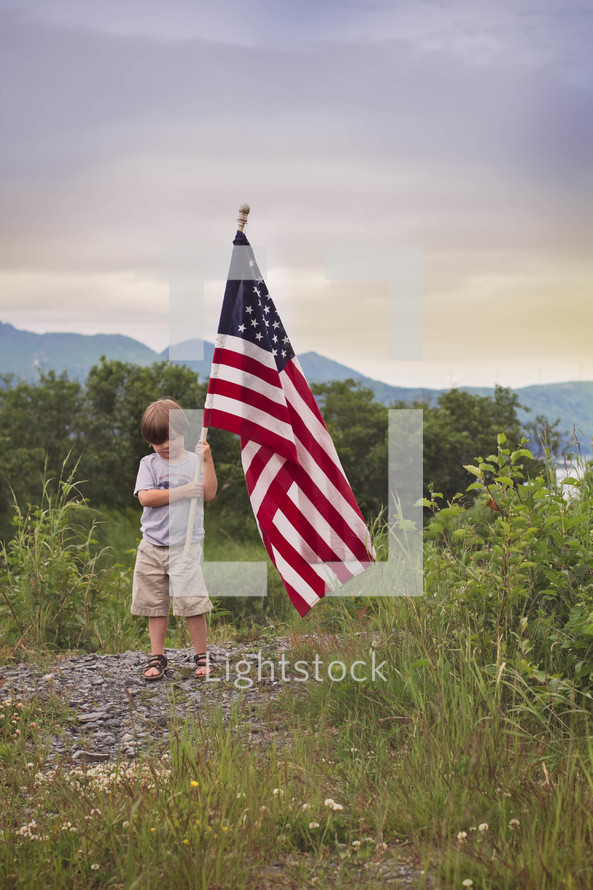 boy child carrying an American flag