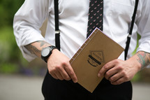 "A man holding a notebook titled, ""Reverend."""