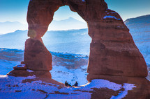 sitting under a red rock arch in snow