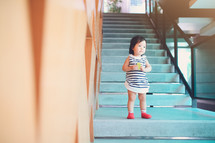toddler girl standing on stairs