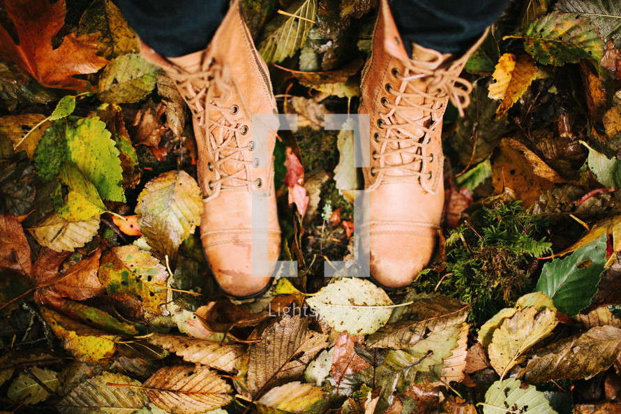 A person standing in boots surrounded by autumn leaves