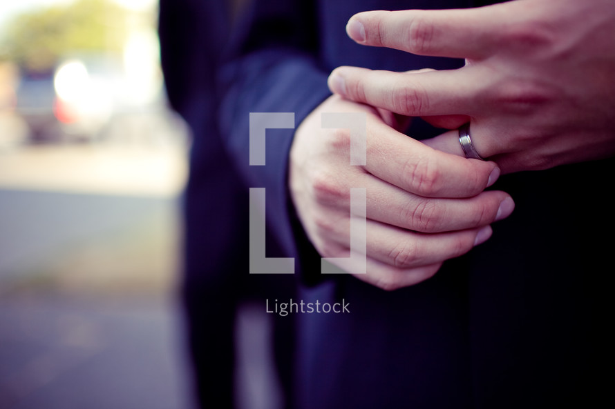 man with his hands on his wedding band